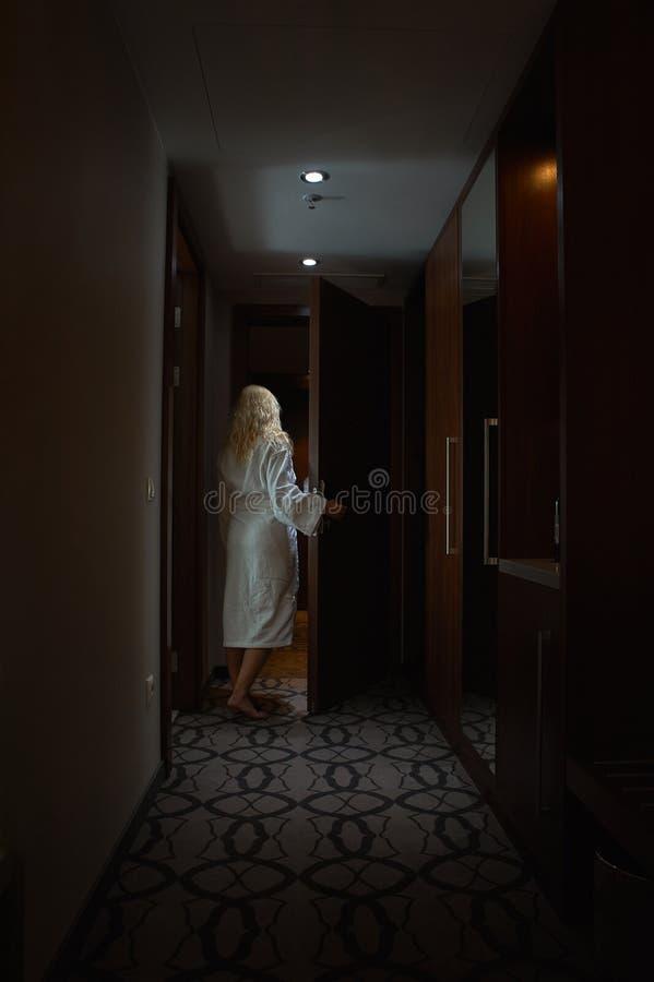 Den barfota kvinnan med den vita badrocken öppnar dörren royaltyfri foto