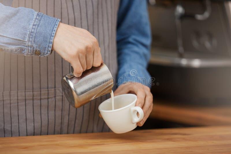 Den Barista danandekoppen av latte som häller mjölkar in i koppen royaltyfri bild