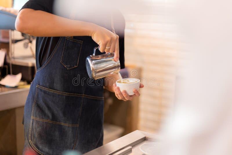 Den Barista handen häller mjölkar framställning av lattekonstkaffe på kafét arkivfoto