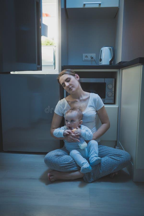 Den barn tröttade modern avverkar sovande, medan hennes matning, behandla som ett barn pojken med mjölkar på natten royaltyfria foton