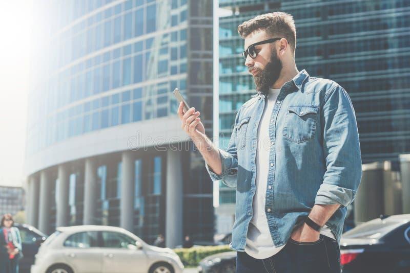 Den barn uppsökte affärsmannen i solglasögon står på stadsgatan och använder smartphonen I bakgrund är modern byggnad royaltyfri bild