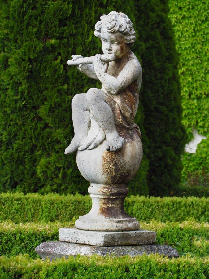 Den barocka statyn i slott parkerar, pysen som spelar flöjten arkivfoton