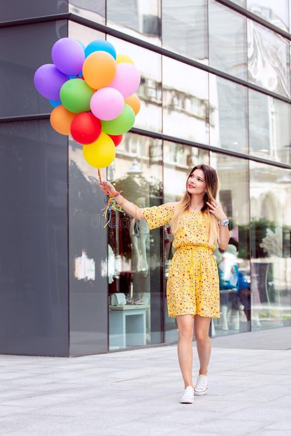 Den Beaituful flickan går i staden med ballons i hand royaltyfri fotografi