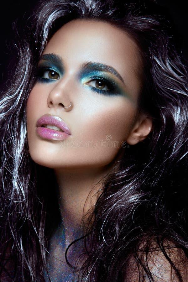 Den Beautyful flickan med blått blänker på hennes framsida royaltyfria bilder