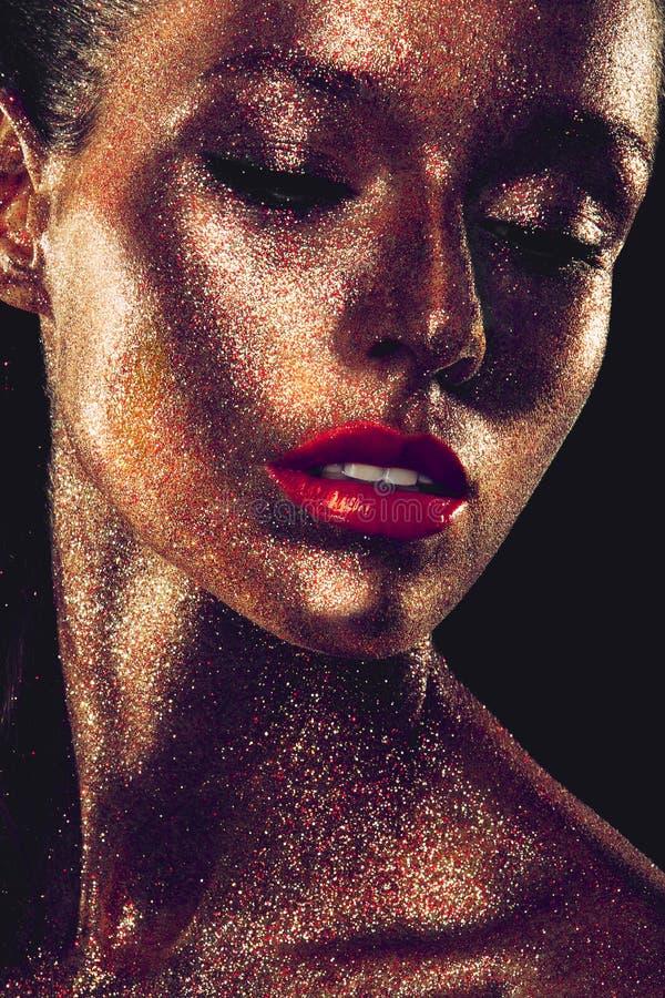 Den Beautyful flickan med guld blänker på hennes framsida arkivbilder