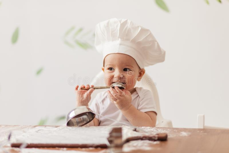 Den begynnande kocken behandla som ett barn den bärande kockhatten för ståenden som spelar med deg på köksbordet arkivbilder