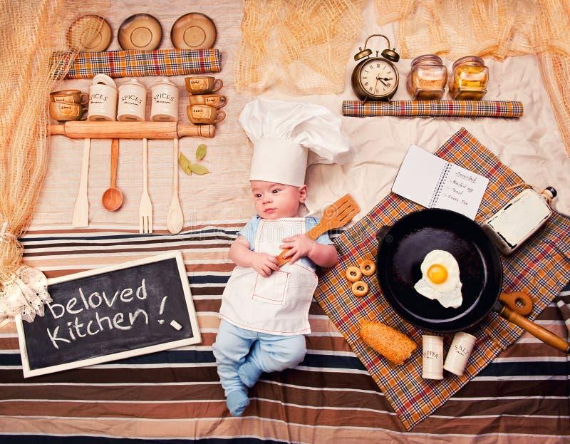 Den begynnande kocken behandla som ett barn det bärande förklädet för pojkeståenden och kockhatten royaltyfria bilder