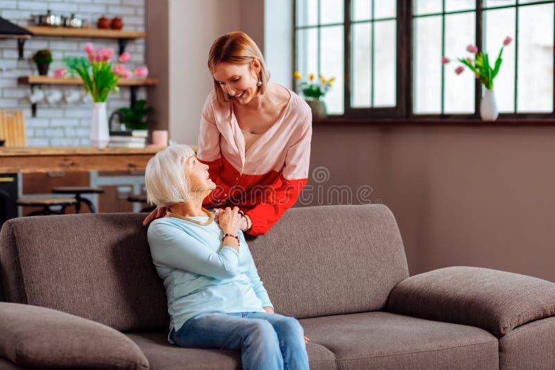 Den behagfulla äldre mamman med grått hår som rymmer lovingly dottern, gömma i handflatan arkivfoton