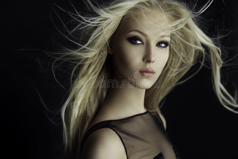 Den behagfulla blonda flickan i perfekt utgör med hår spritt av vinden som isoleras på en svart bakgrund royaltyfria foton