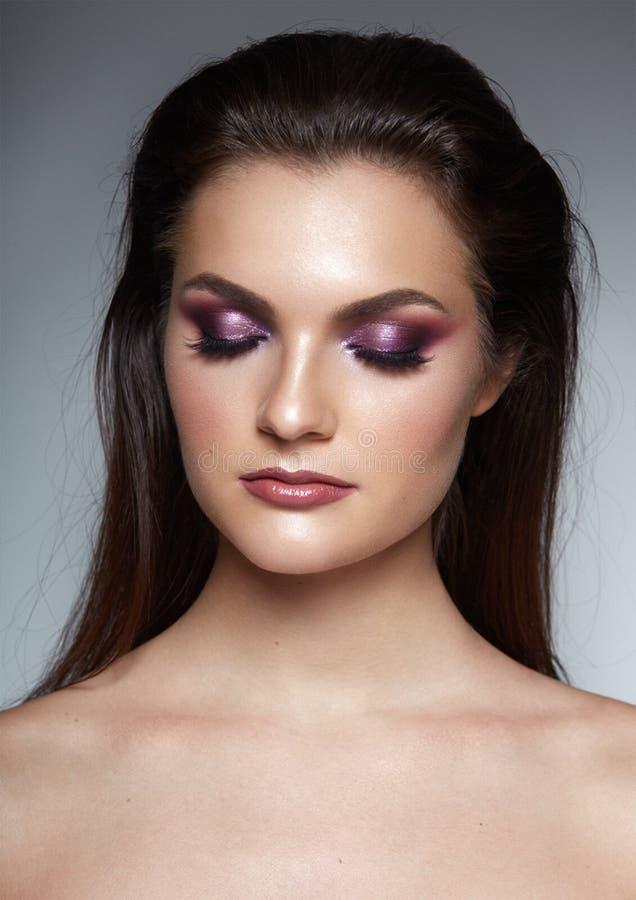 Den behagfulla unga kvinnan med cosed ögon, poserar säkert med hairstule, och perfekt utgör, isolerat på en grå bakgrund arkivfoton
