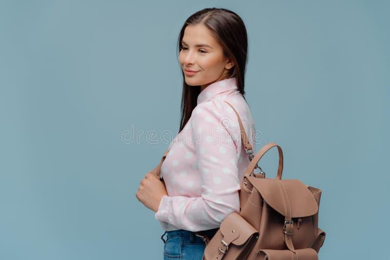 Den behog kvinnan med mörkt hår, ser lyckligt in i avstånd, står från sidan med ryggsäcken som går att resa, iklätt stilfullt arkivfoto