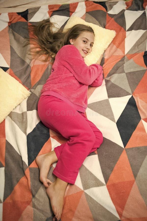 Den bekv?ma pyjamasen f?r kopplar av B?r den lilla ungen f?r flickan mjuk gullig pyjamas, medan koppla av p? s?ng Sk?mtsamt behan royaltyfria bilder