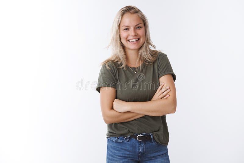 Den bekymmersl?sa karismatiska blonda kvinnan som skrattar korsa joyfully armar p? br?stkorgen som pleasantly stirrar p? kameran  arkivbilder