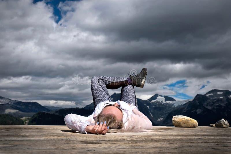 Den bekymmerslösa kvinnan som ner ligger bland berg som tar ta sig en tupplur royaltyfri foto