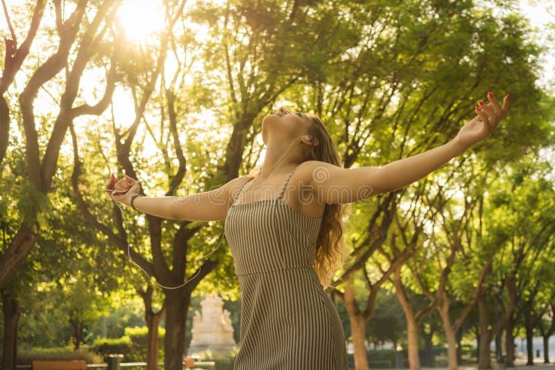 Den bekymmerslösa unga attraktiva kvinnan med hennes armar lyftte mening fri, medan lyssnande musik i parkerar royaltyfri fotografi