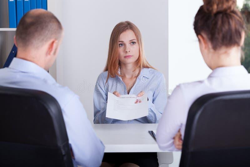 Den bekymrade flickan visar hennes CV royaltyfri foto