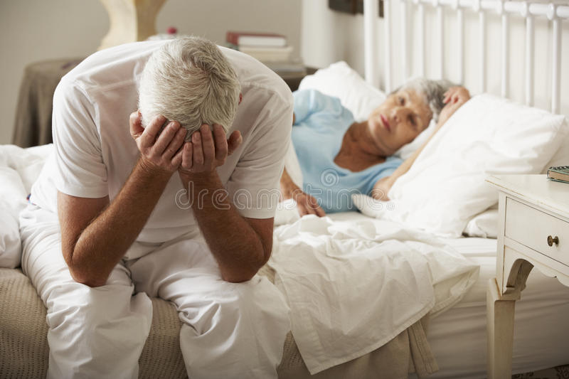 Den bekymrade höga mannen sitter på sömnar för sängstundfru arkivbilder