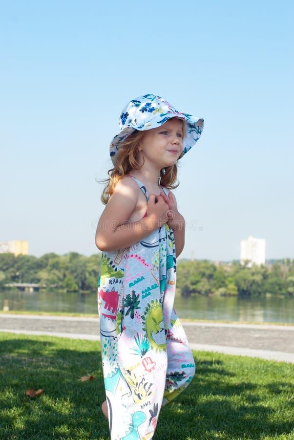 Den bekymrade lilla flickan i en hatt spelar på den gröna gräsmattan arkivbild