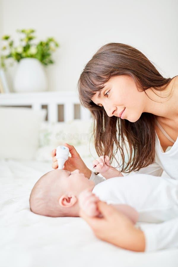 Den bekymrade modern mäter feber i spädbarn royaltyfria foton