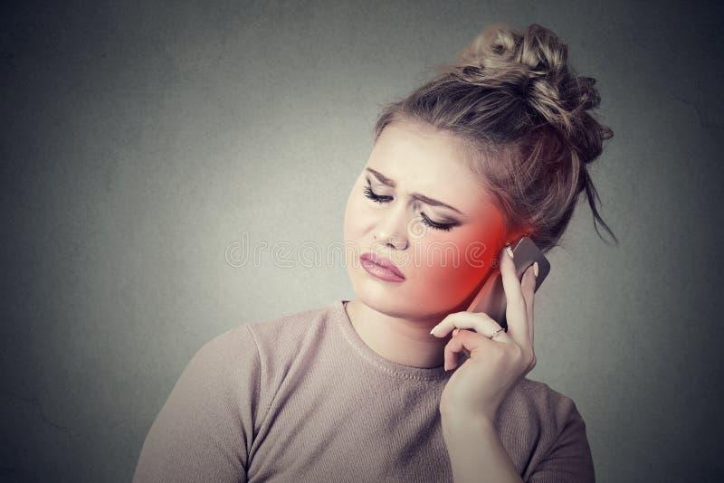Den bekymrade unga kvinnan som talar på mobiltelefonen som den har, smärtar huvudvärk royaltyfri fotografi