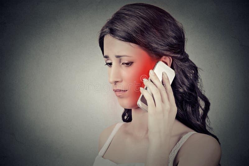 Den bekymrade unga kvinnan som talar på mobiltelefonen som den har, smärtar huvudvärk arkivfoto