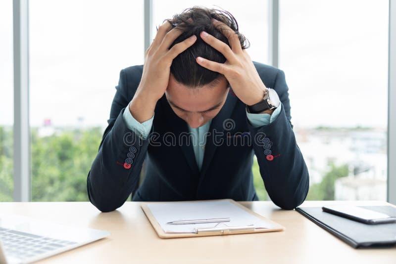 Den belastade affärsmannen rymmer hans huvud med hans händer arkivfoto