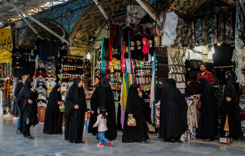 Den berömda iranska marknadsbasaren och kvinnor i svart chodor väljer gods royaltyfria bilder