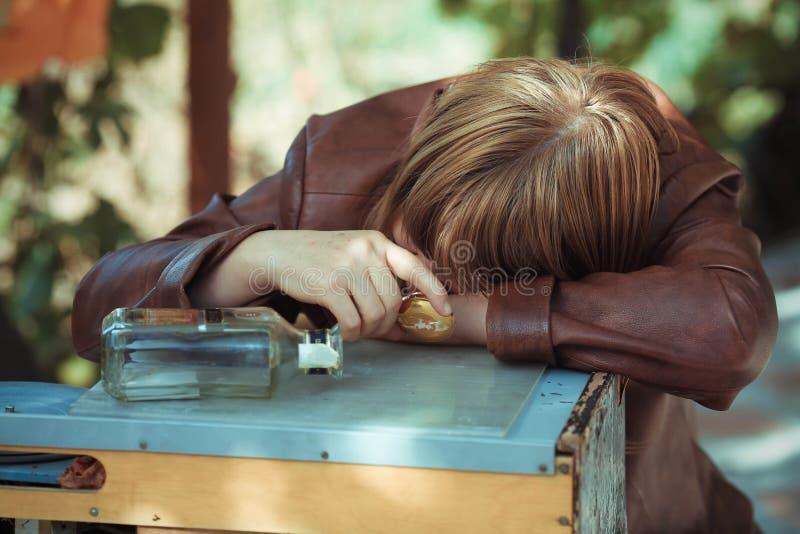 Den berusade kvinnan som avverkar sovande på en tabell royaltyfri bild