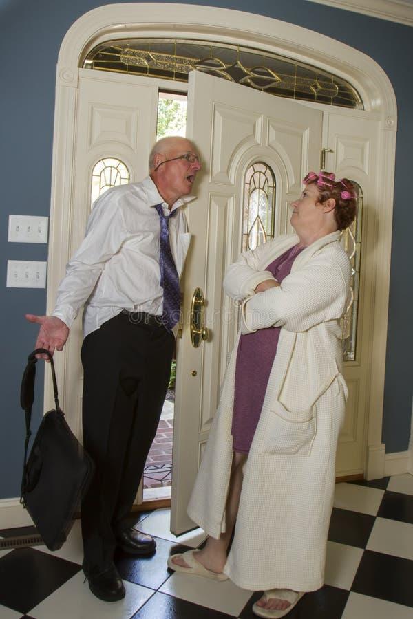 Den berusade mannen möter den ilskna frun på ytterdörren royaltyfri foto