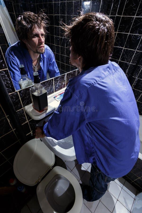 Den berusade mannen ser honom i spegeln royaltyfri foto