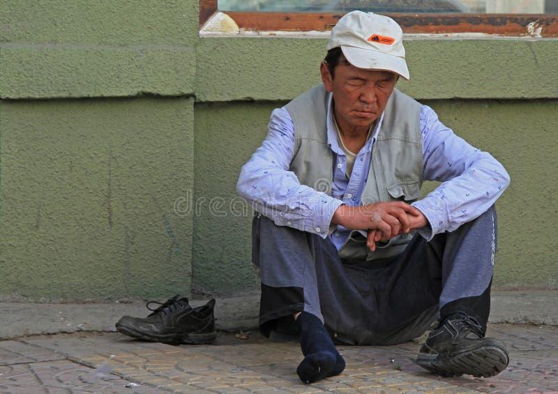 Den berusade mannen sitter på asfalt i Ulaanbaatar royaltyfri foto