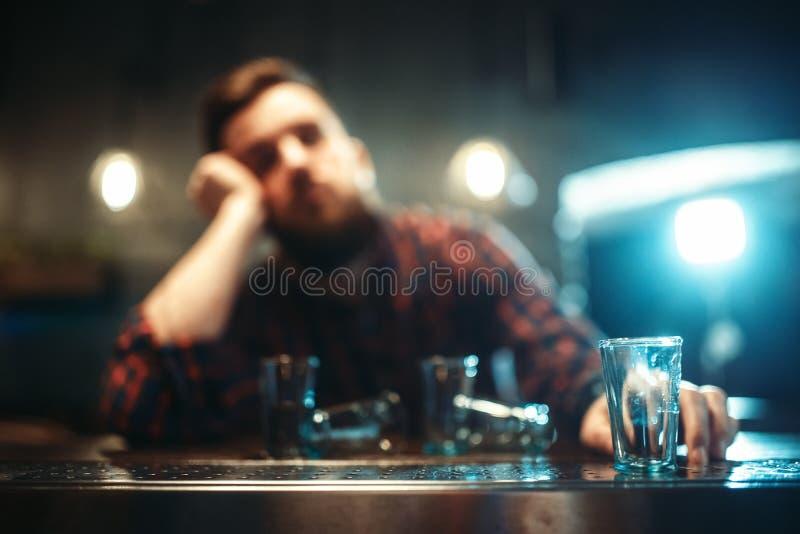 Den berusade mannen sover på stångräknaren, alkoholböjelse royaltyfri fotografi
