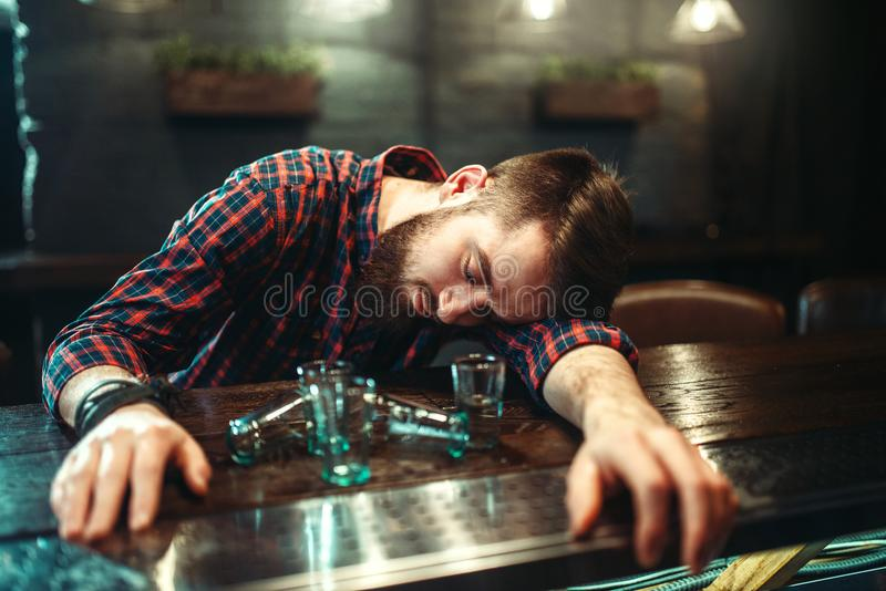 Den berusade mannen sover på stångräknaren, alkoholböjelse arkivbild