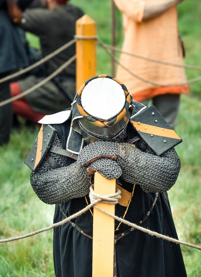 Den besegrade riddaren bugade hans huvud efter striden Den trötta riddaren står med ett nedböjt huvud arkivfoto