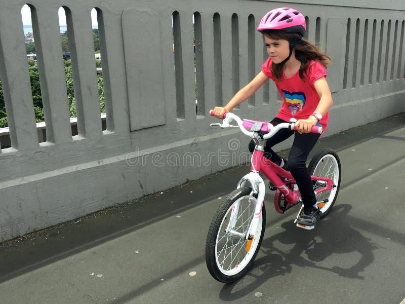 Den beslutsamma unga flickan rider en cykel royaltyfri bild