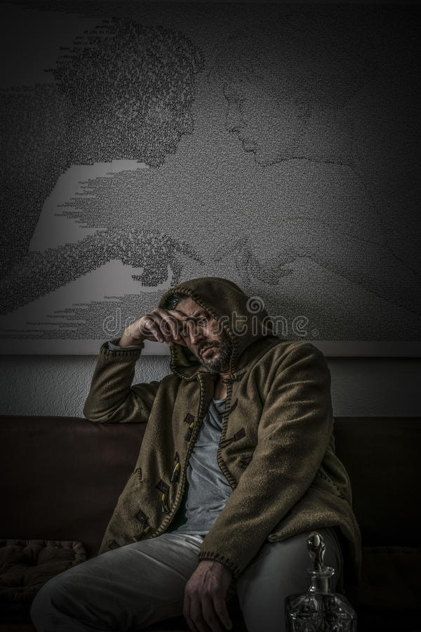 Den besvikna mannen med en huv och tömmer den inristade glasflaskan av alkohol arkivfoto
