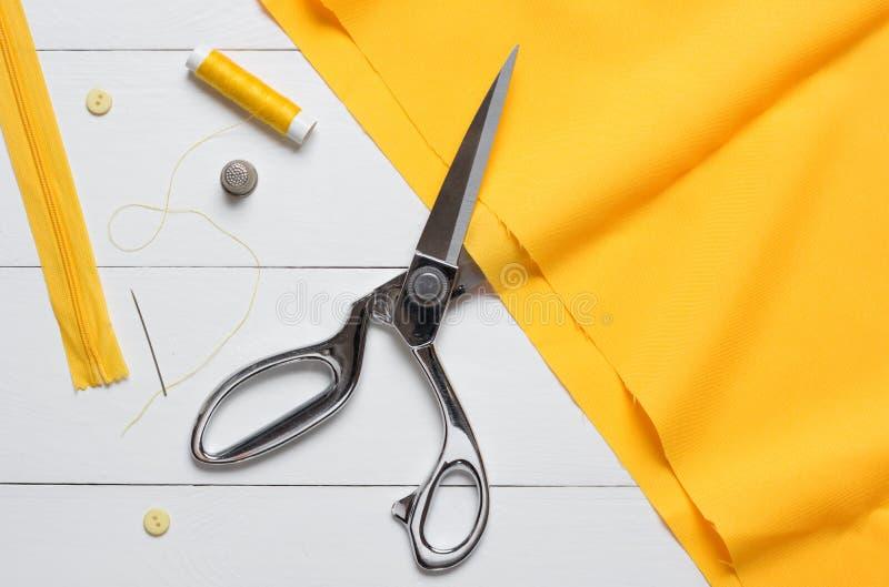 Den bitande textilen eller den fina torkduken med en skräddare scissors på trät fotografering för bildbyråer