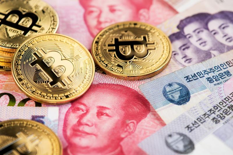 Den Bitcoin cryptocurrencyen på nordkoreanska segrade och Kina Yuan Renminbi valutasedlar stänger sig upp bild arkivfoto