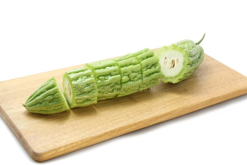 Den bittra melon- eller bitterhetkalebassen skivade ‹för †på träskärbrädor på vit bakgrund royaltyfri bild