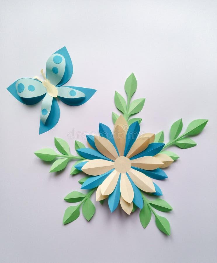 Den blåa blomman och gräsplanbladet med fjärilen skyler över brister konst som isoleras på arkivfoto