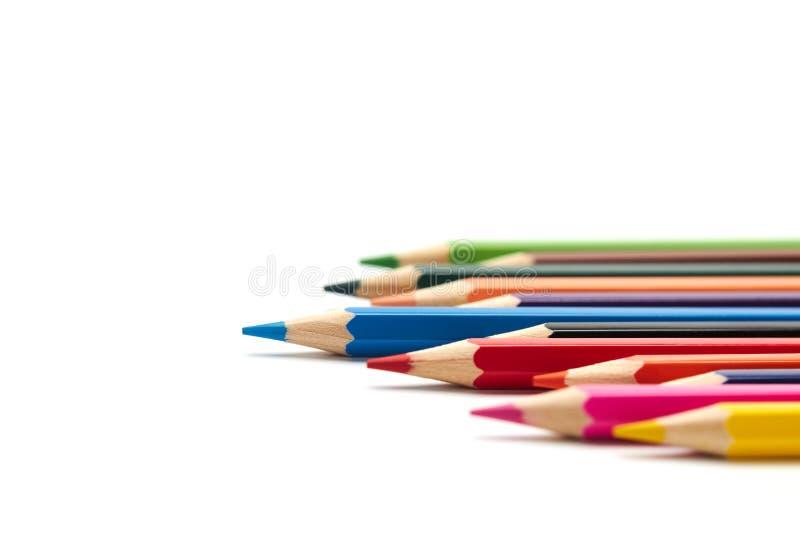 Den blåa blyertspennan står ut från ett antal andra kulöra blyertspennor som ligger på en isolerad vit bakgrund royaltyfri foto