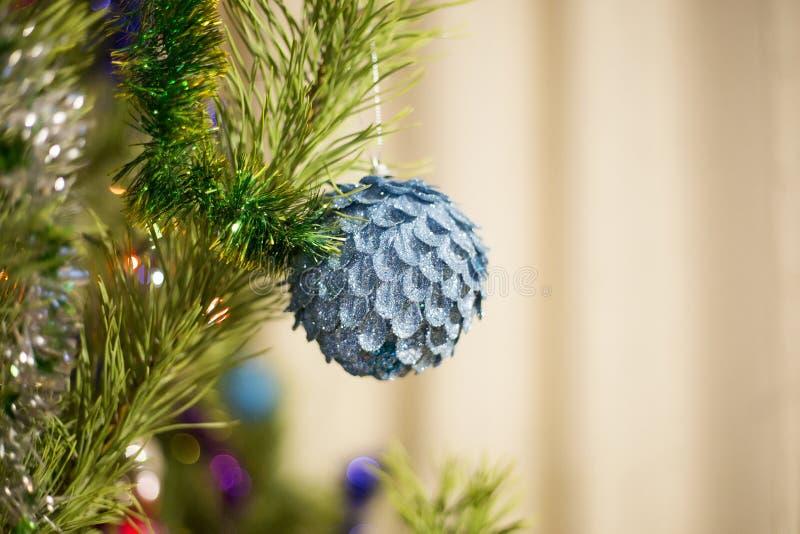 Den blåa härliga bollen väger på gräsplanträdet för det nya året som dekoreras med girlander och glitter royaltyfri foto