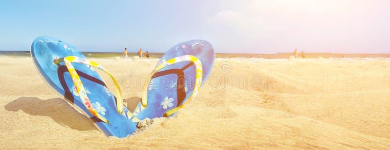 Den blåa sandalen bläddrar misslyckande på den vita sandstranden med blå havs- och himmelbakgrund i utrymme för kopia för sommars royaltyfria bilder