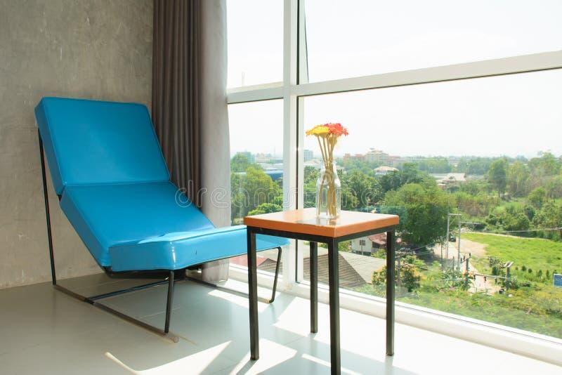 Den blåa soffan och blomman kopplar av in tid royaltyfri foto