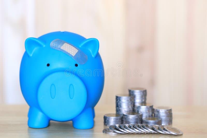 Den blåa spargrisen som fästas till murbruken på huvudet, sparar pengar för medicinsk försäkring och hälsovårdbegrepp arkivfoto