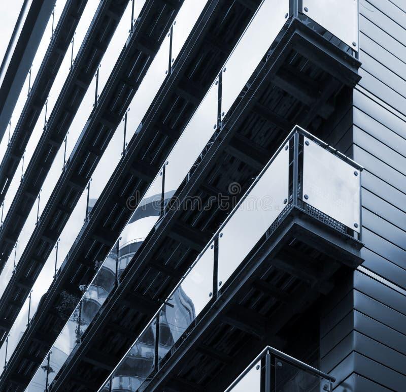 Den blåa tonade hörnsikten av moderna lägenheter med stilfullt exponeringsglas paneled balkonger reflekterar närliggande stads- b royaltyfri bild
