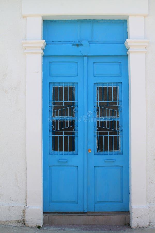 Den blåa ytterdörren i vit stenar väggen royaltyfri foto