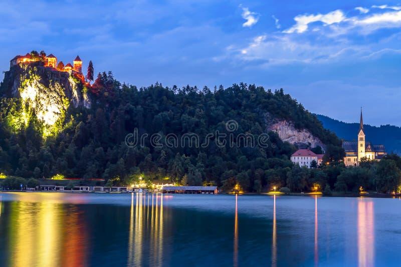 Den blödde slotten som tänds under blå timme royaltyfria foton