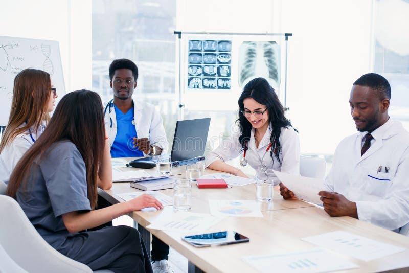Den blandras- gruppen av yrkesmässiga medicinska doktorer har ett möte på konferensrum i sjukhus Laget av ungt royaltyfri bild