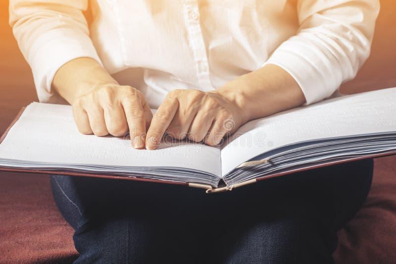 Den blinda kvinnan läste boken som var skriftlig i tonad blindskrift royaltyfria bilder